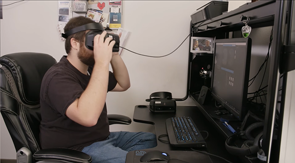 E McNeill sitting in front of computer with VR headset on
