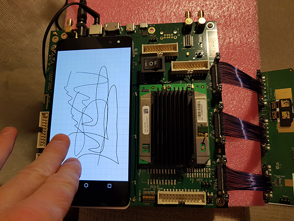 Two fingers draw lines on phone screen attached to development board