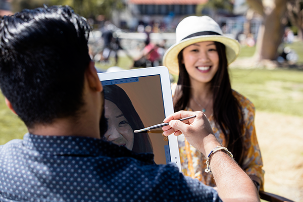 Man in blue shirt paints portrait of young woman wearing white hat