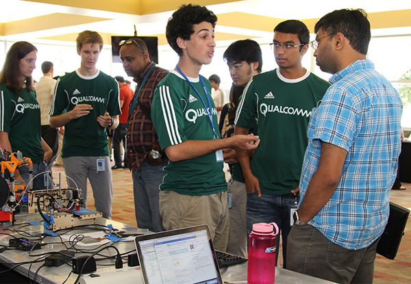 Cyrus Tabrizi and teammates in green Qualcomm shirts talking with man at Qualcomm IdeaQuest