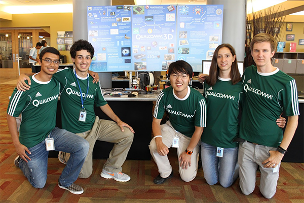 Four males and 1 female in green shirts with Qualcomm logo kneeling in front of project board