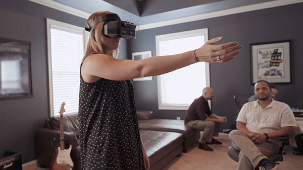 Woman wearing virtual reality headset with arm extended