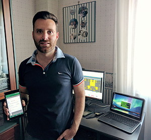 Giuseppe Romano with Android phone, with laptop and desktop computer stations behind him