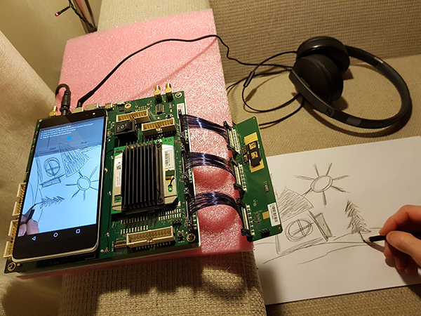 Development board with mobile phone screen and headphones on left while man draws on paper on right side