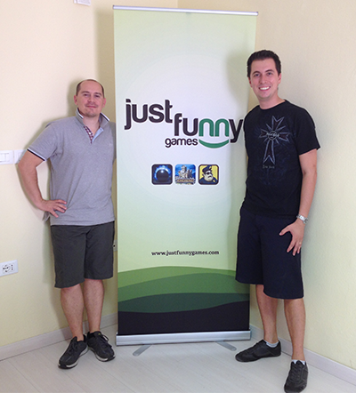 Two men stood next to Just Funny Games banner