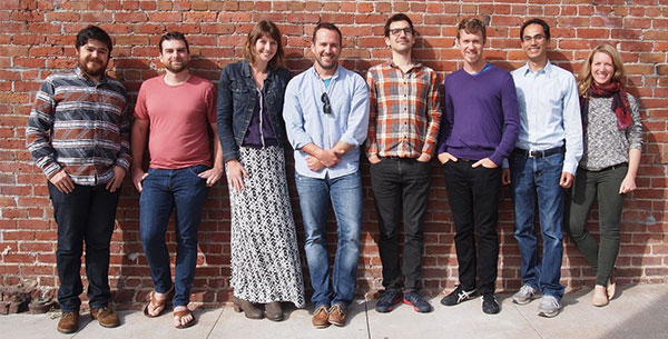 8 members of the Knit Health team standing in front of brick wall
