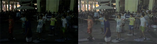 dark image of children dancing outdoors in front of crowd