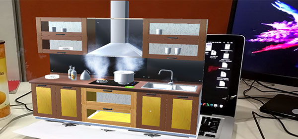 Computer generated image of kitchen superimposed over desk with laptop and monitor