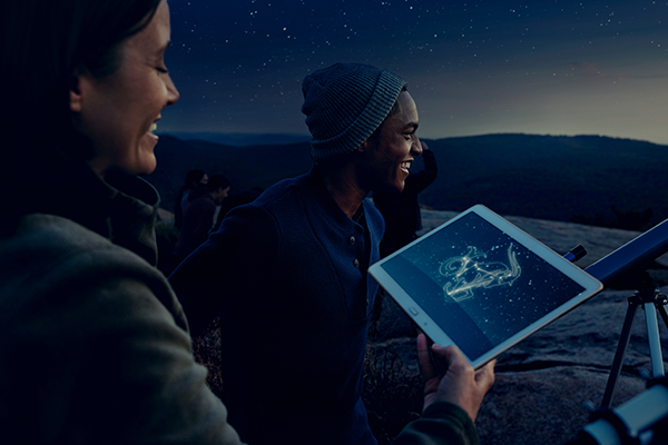 Two astronomers look at night sky and hold a mobile tablet